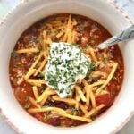 bowl of campfire chili with sour cream and cheese on top.