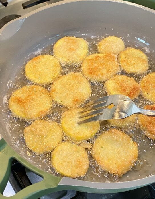 squash being fried in a skillet.