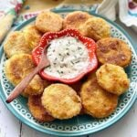 fried squash on a blue plate with ranch dip in the middle.