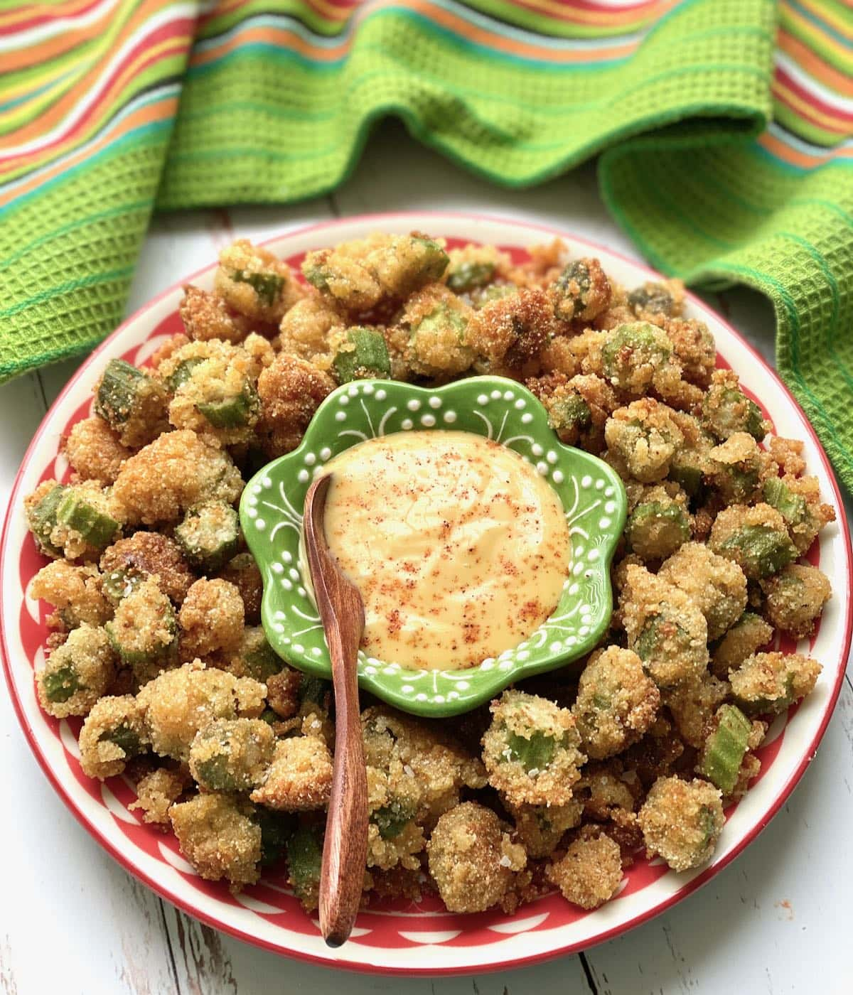 fried okra surrounding a green dish of honey mustard sauce.