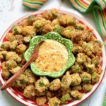 honey mustard dip in the middle of a plate of fried okra.