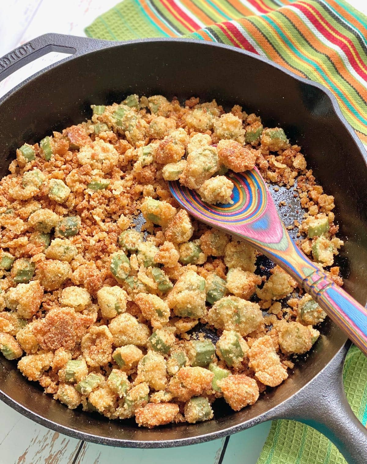 fried okra in a black cast iron skillet with a green towel in background.