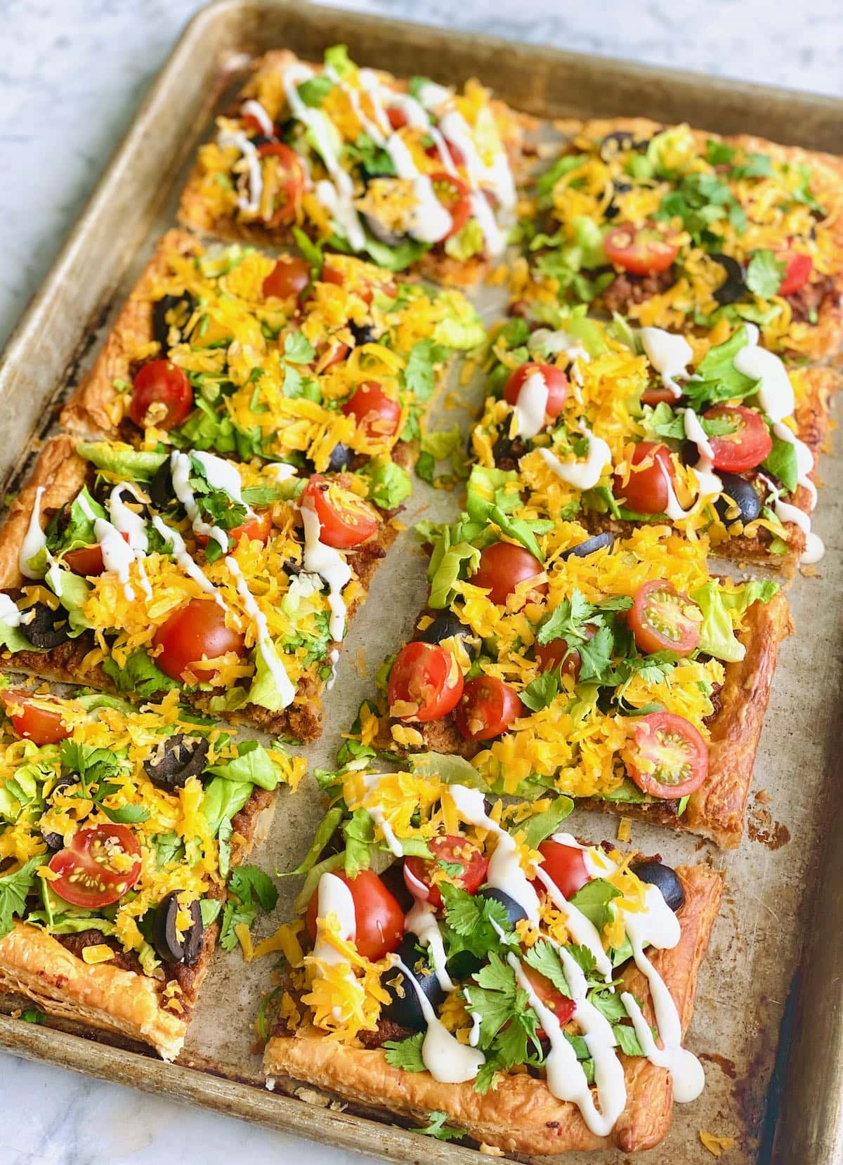 slices of sheet pan taco bake with every other one drizzled in sour cream