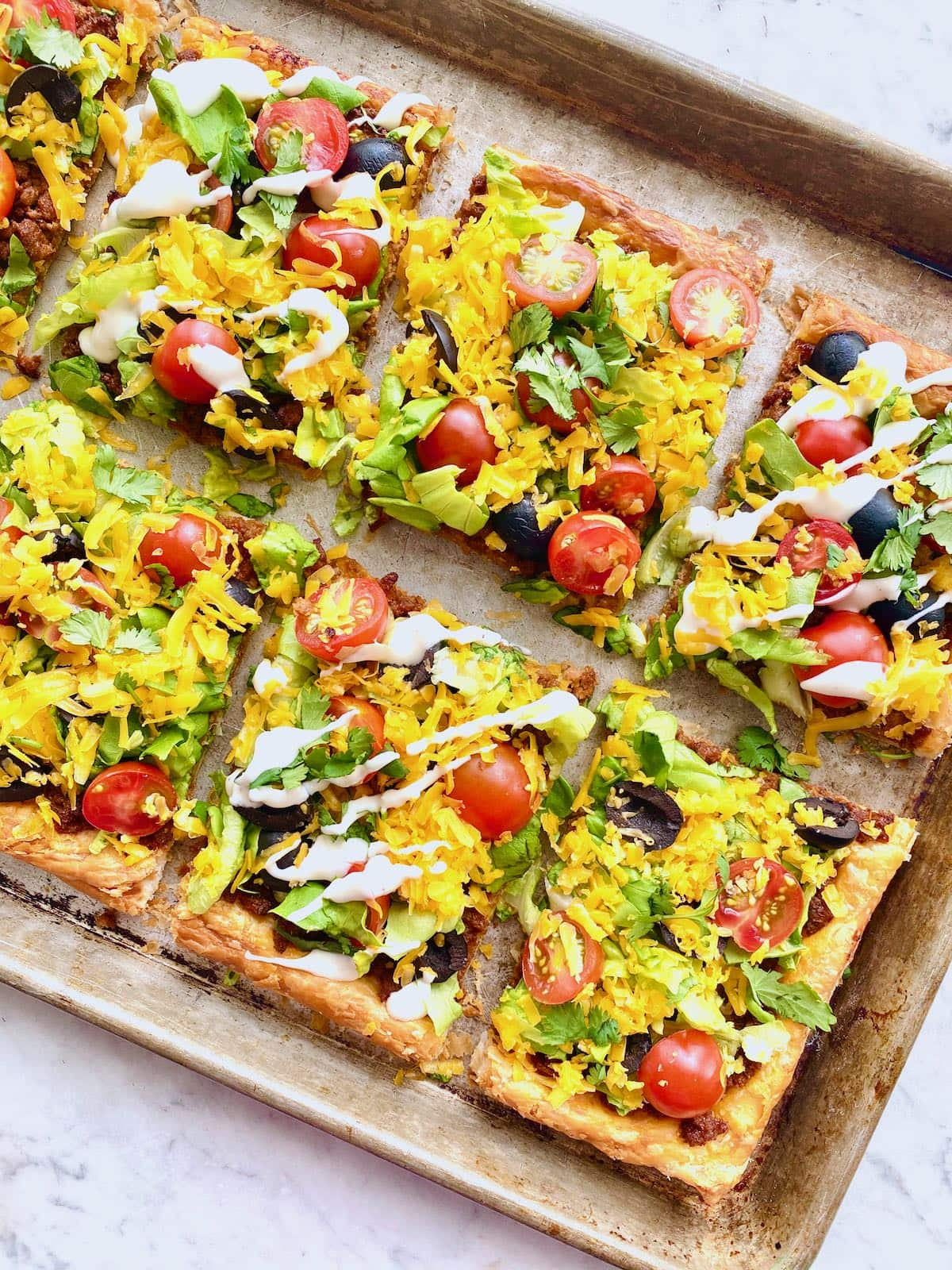 sheet pan filled with puff pastry tacos including toppings like lettuce, tomatoes and cheese with a sour cream drizzle