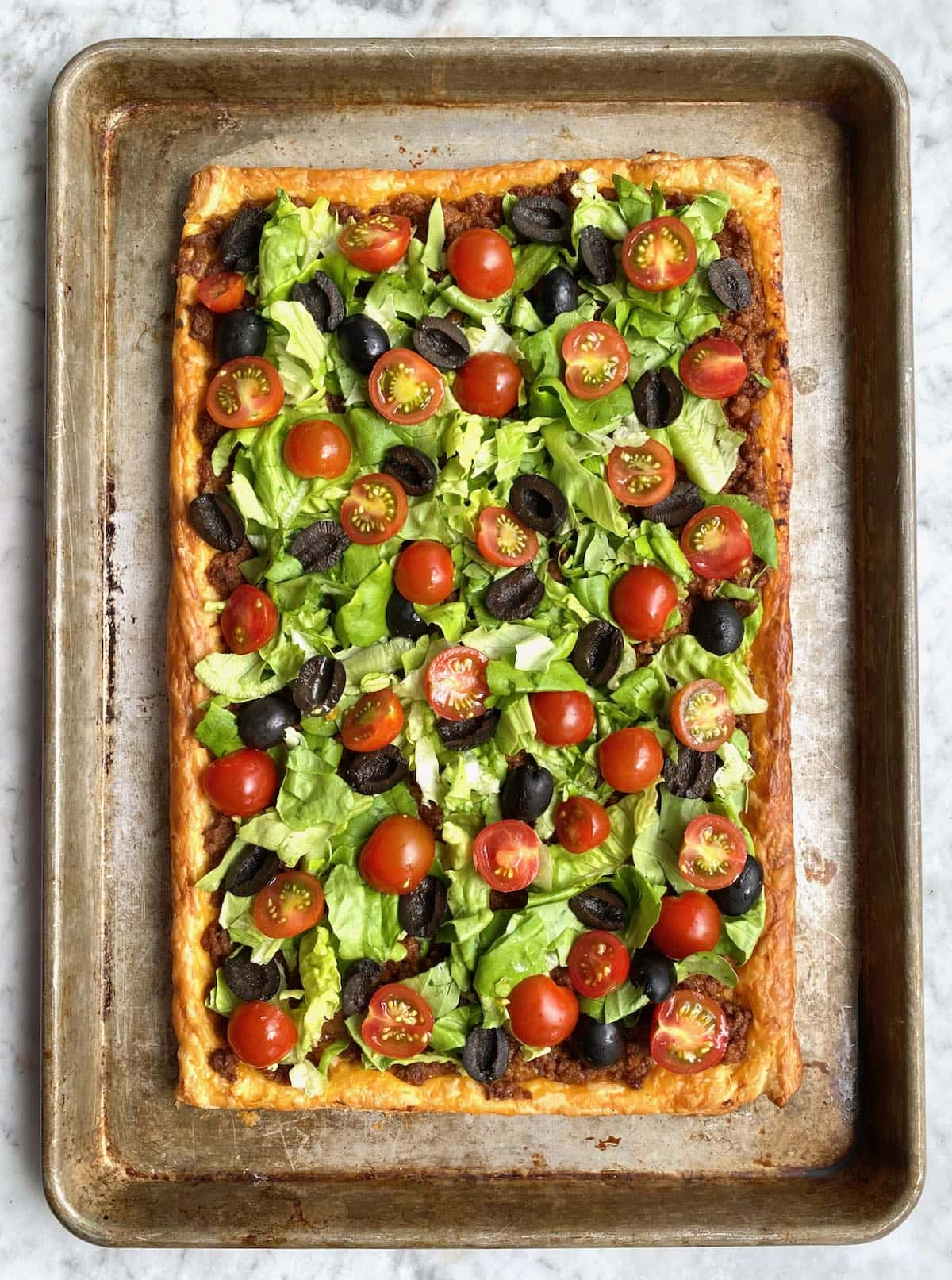 sheet of puff pastry topped with lettuce, tomatoes and olives