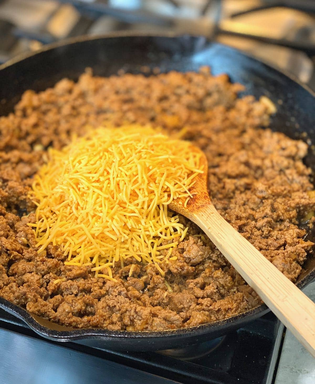 skillet filled with ground turkey and taco seasoning with cheese on top