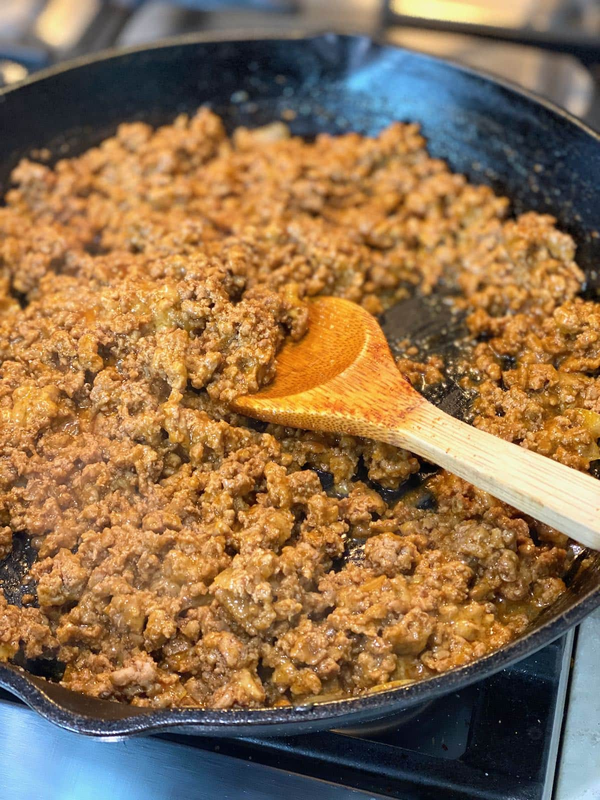 black cast iron skillet with ground turkey that has been mixed with seasoning and cheese