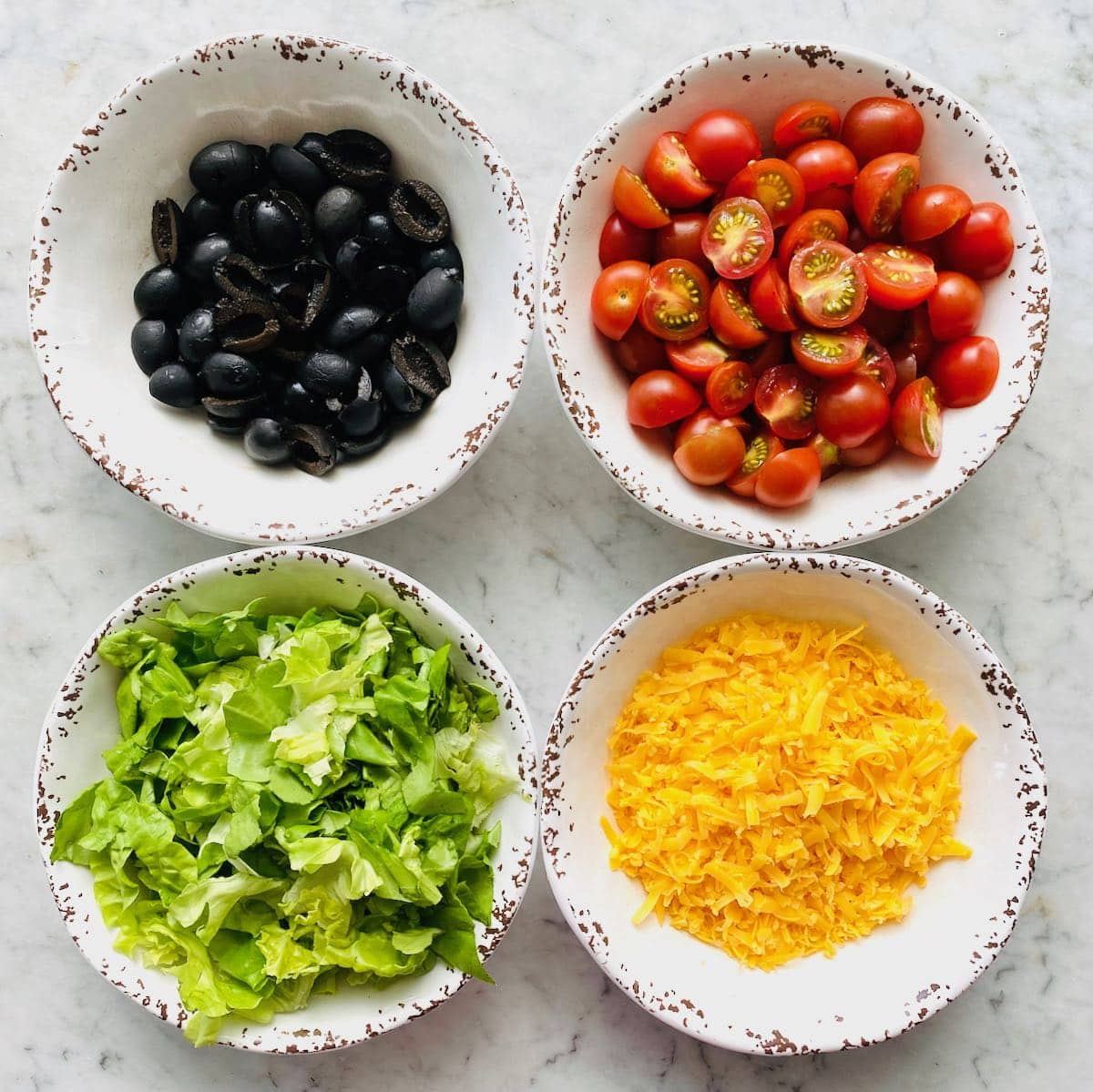 four white bowls filled with different taco toppings like olive, tomatoes, lettuce and cheddar cheese