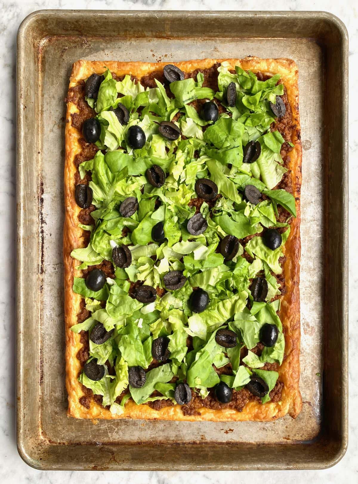 pastry crust topped with lettuce and olives on a sheet pan