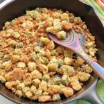 fried okra in a cast iron skillet with a colorful spoon.