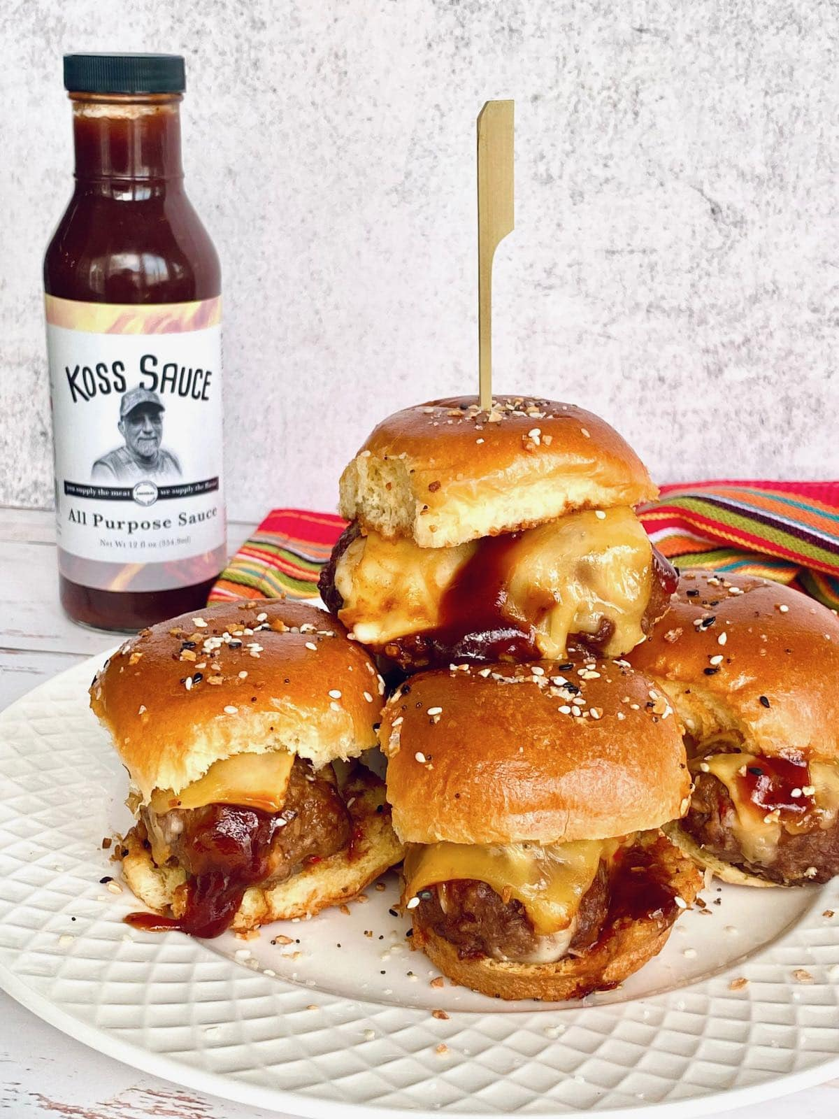 cheesy meatball sliders on a white plate with Koss Sauce in background.