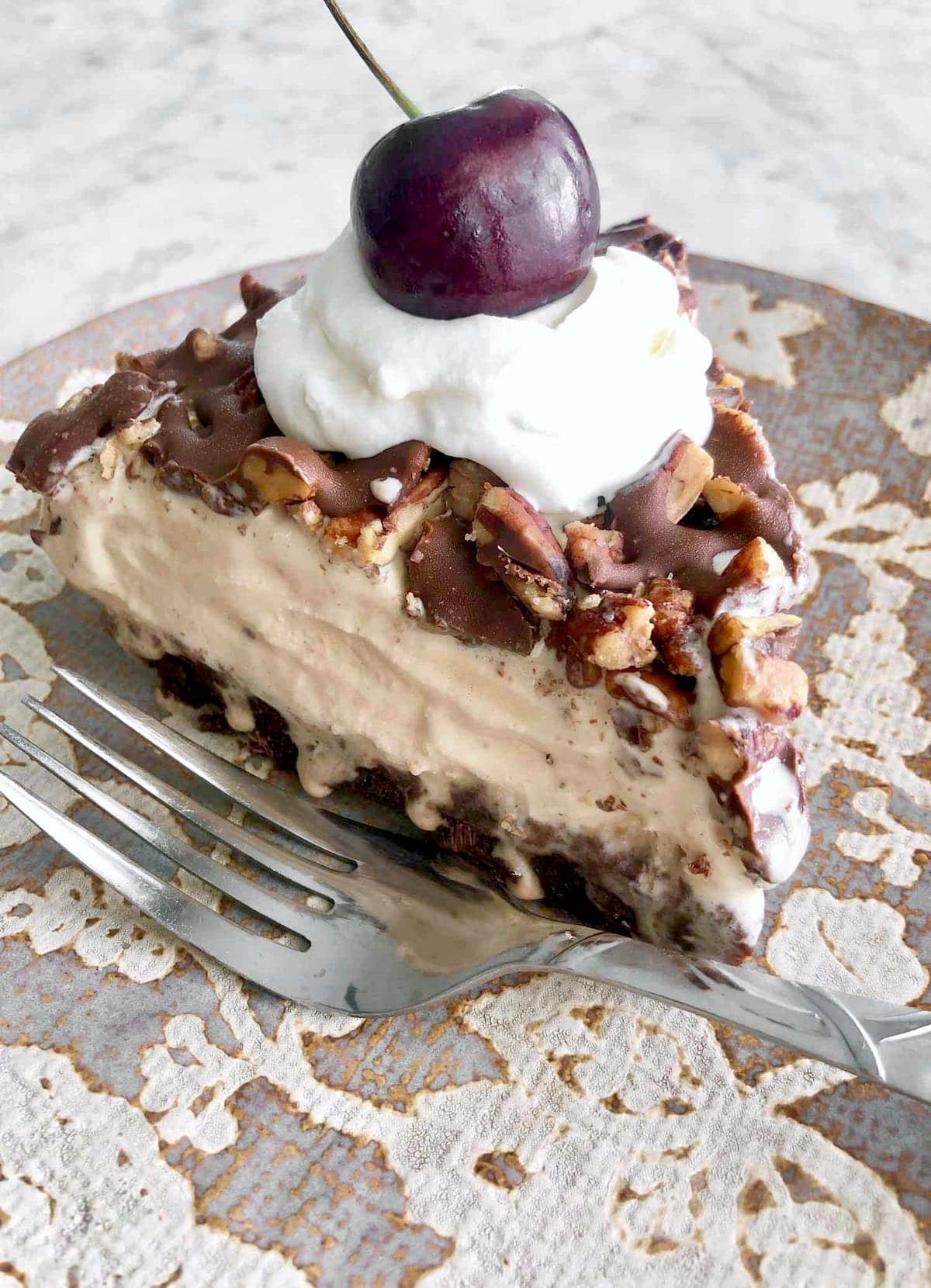 slice of mocha latte ice cream pie on a floral plate.