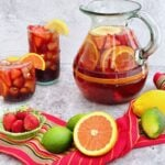 strawberry orange sangria in a pitcher and glasses with fruit in foreground.