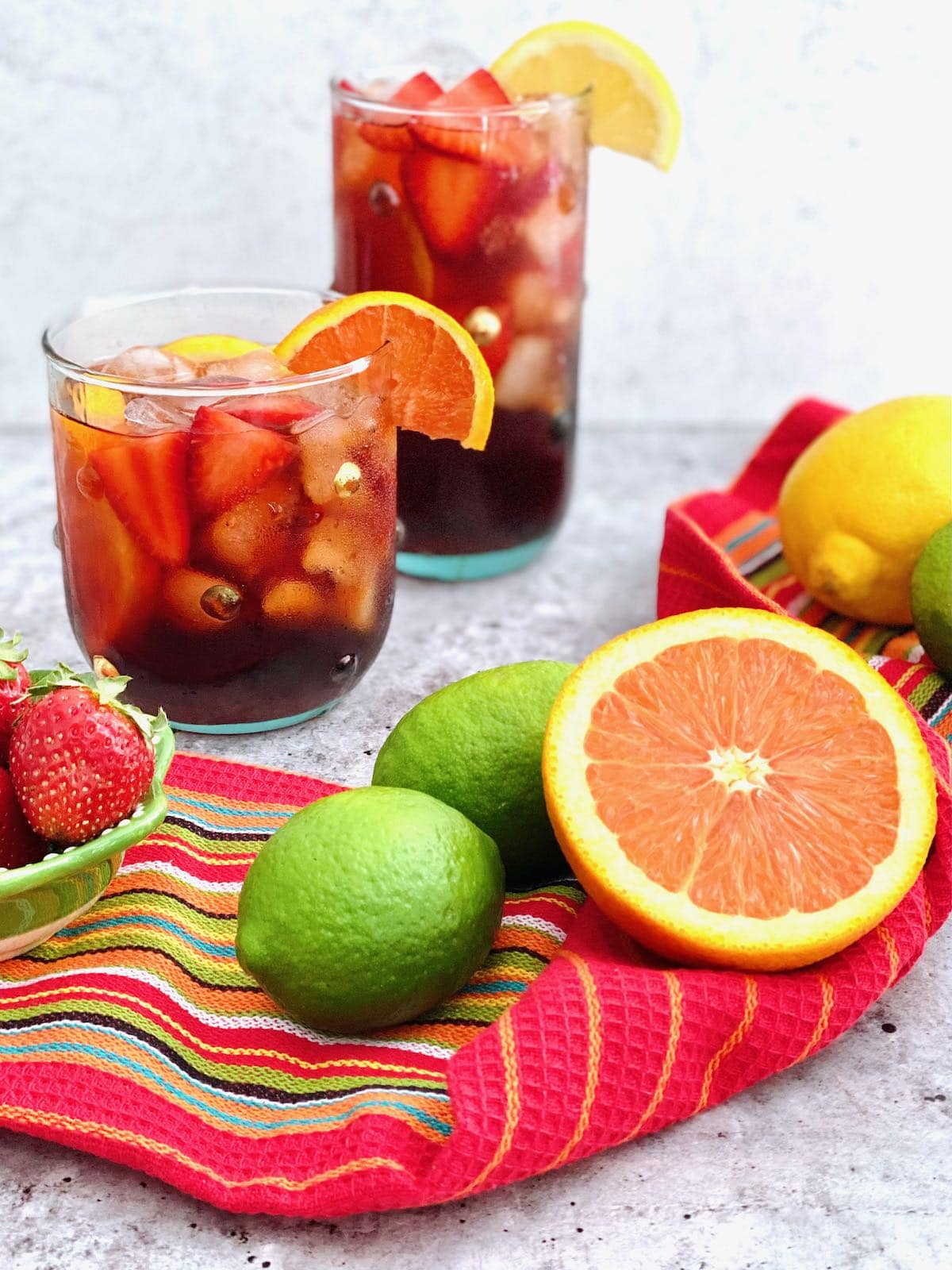 two glasses of sangria with oranges, limes and lemons in the foreground.