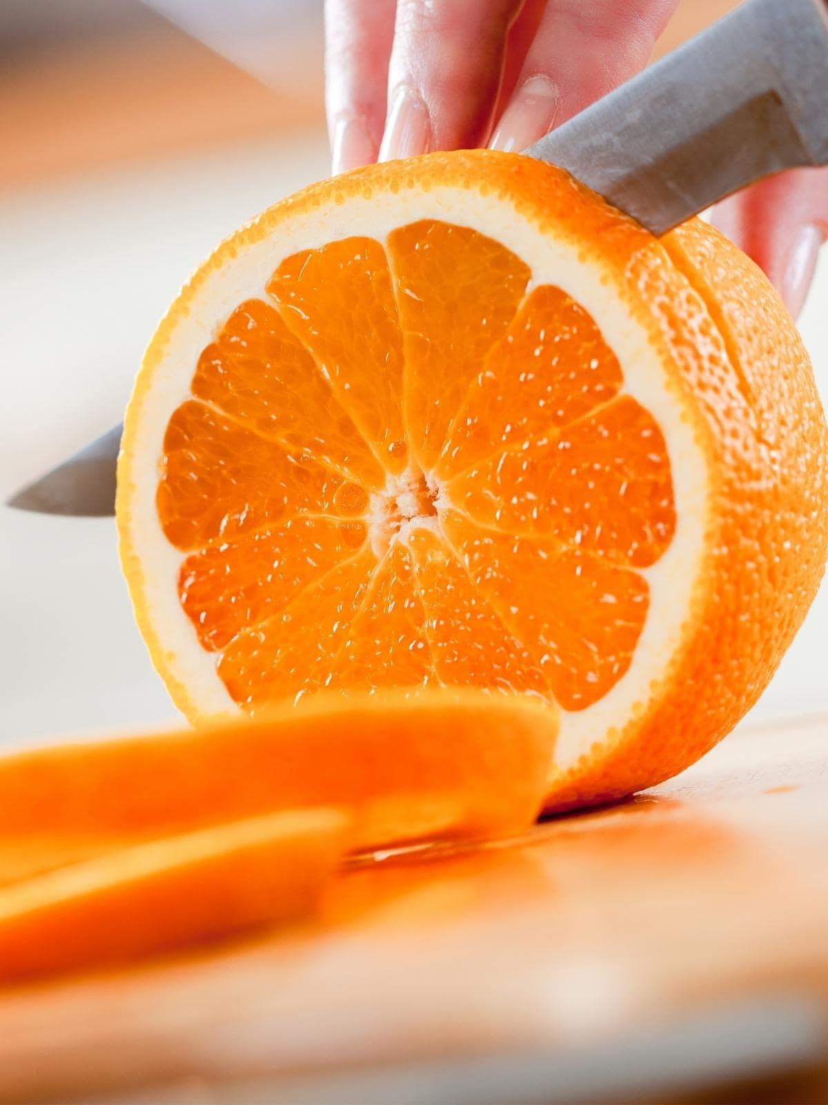 knife cutting circles of oranges.
