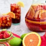 strawberry orange sangria in a pitcher and glasses with fruit in the foreground.