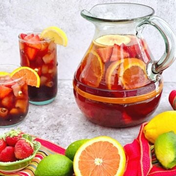 pitcher of strawberry orange sangria poured into two glasses filled with ice.