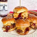 cheesy meatball sliders with Koss Sauce in the background.