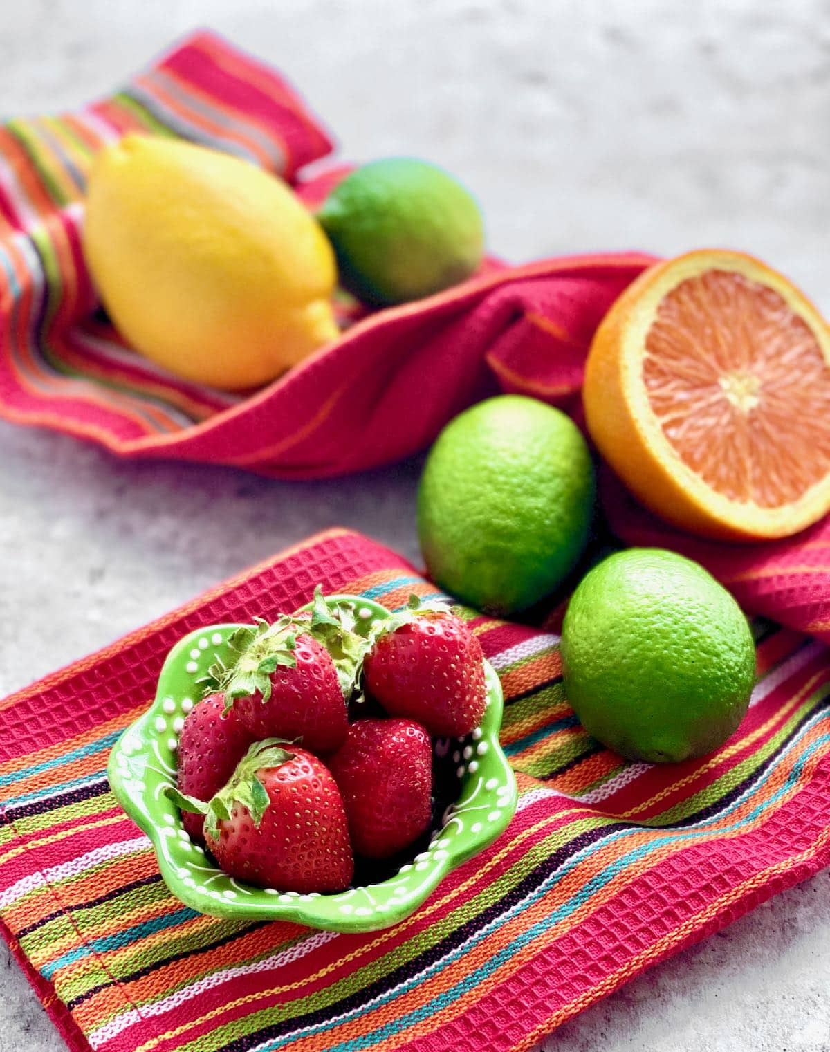 strawberries, oranges, limes and lemons on a red striped cloth.