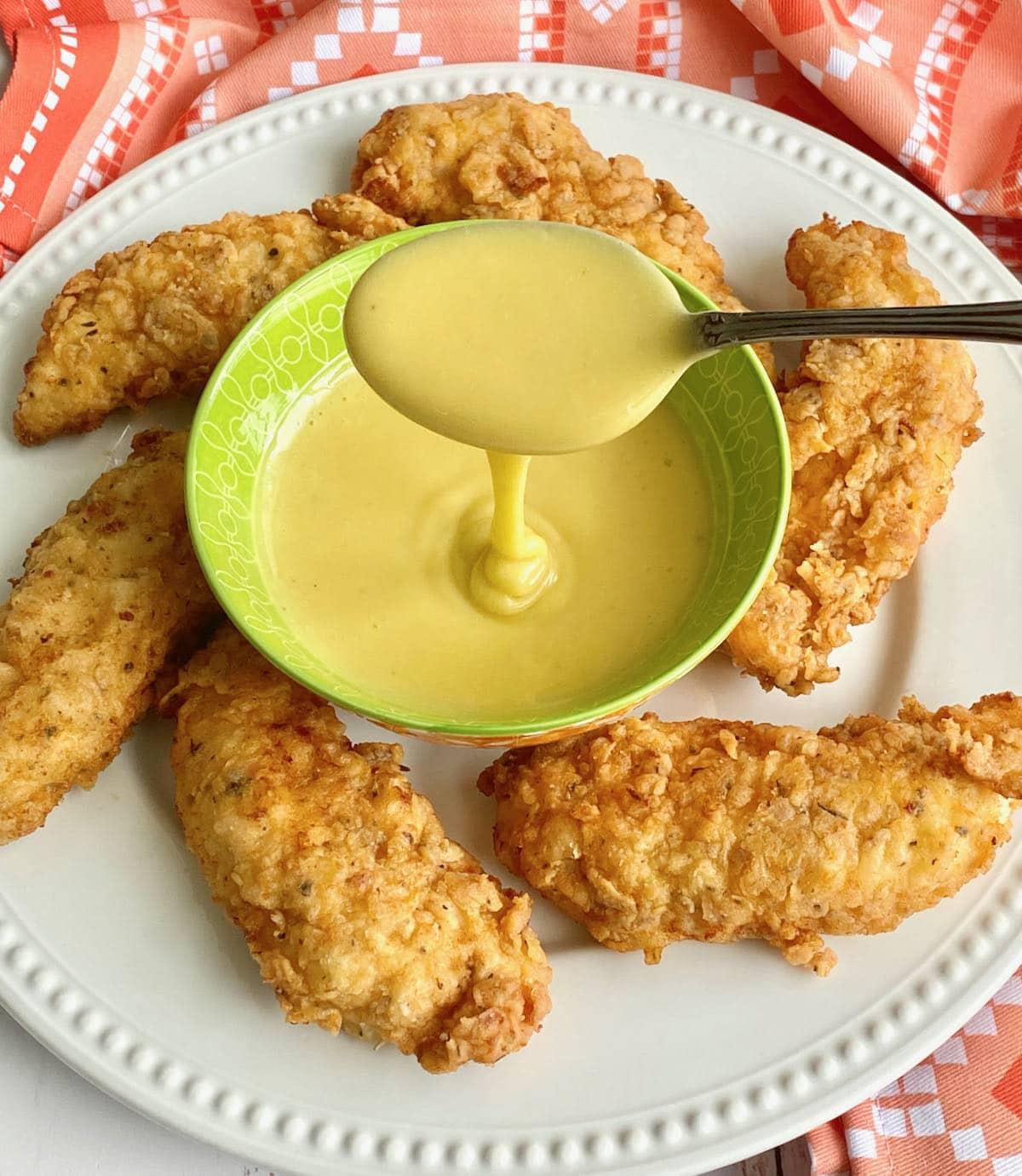buttermilk chicken tenders on a plate surrounding a green bowl of honey mustard sauce.