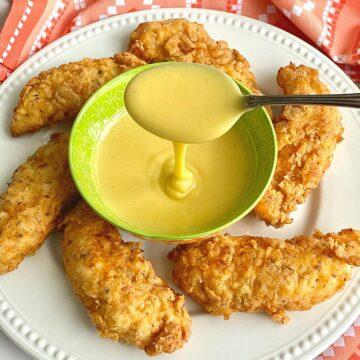circle of buttermilk chicken tenders around a bowl of honey mustard sauce.
