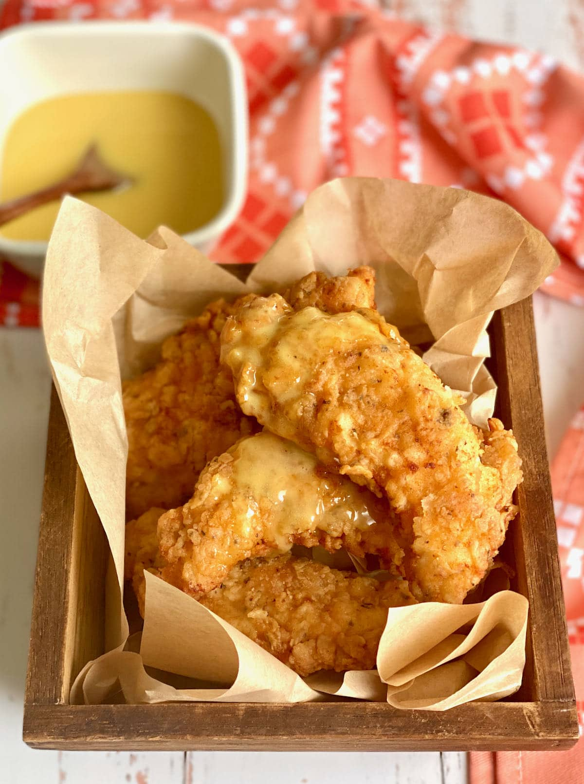 buttermilk chicken tenders in a wooden basket with honey mustard sauce drizzled on top.