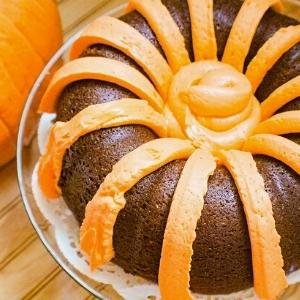orange icing draped over a pumpkin cake to resemble cinderella's carriage.