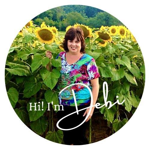 Debi standing in a field of sunflowers