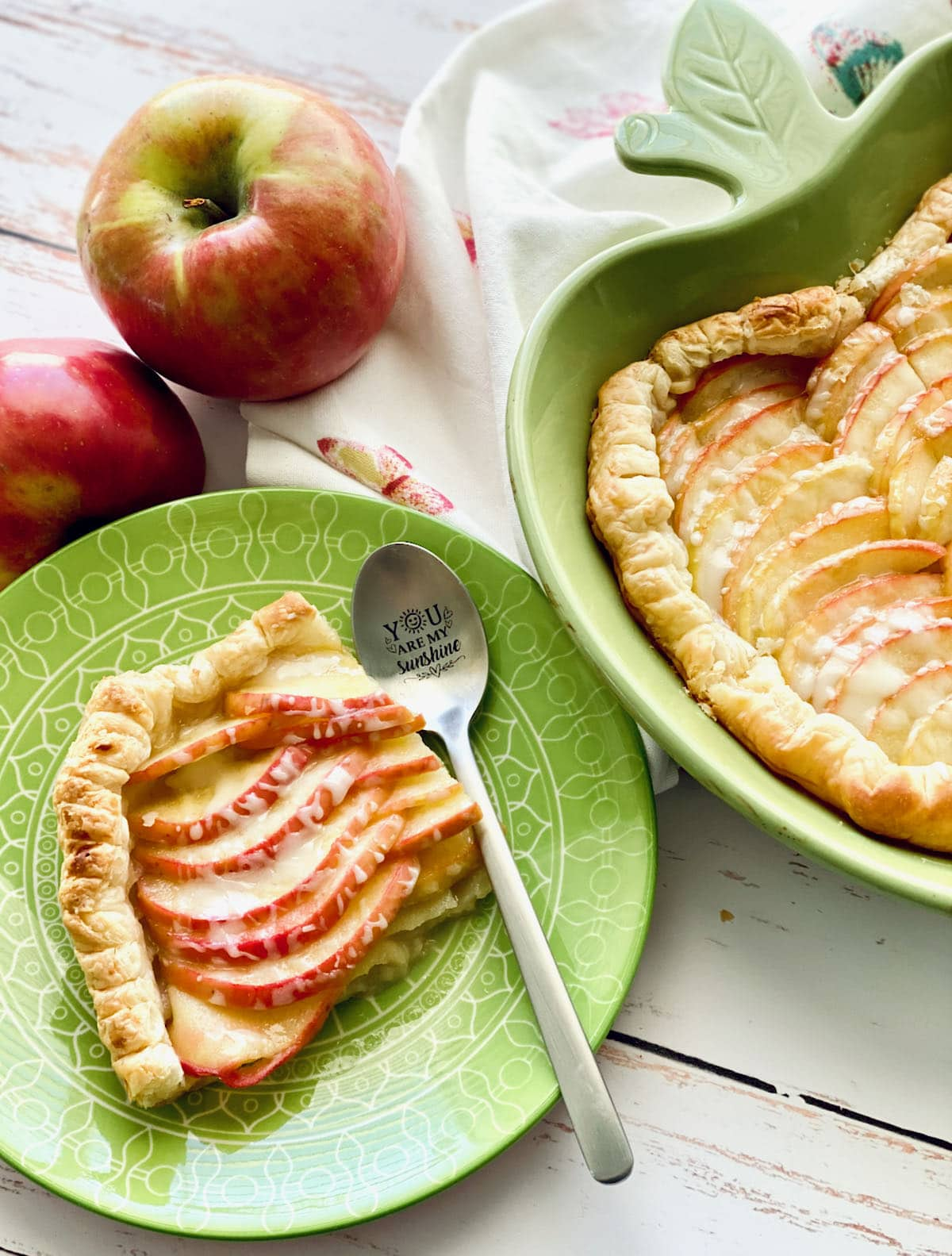 a slice of puff pastry apple tart on a green plate with apples in the background.