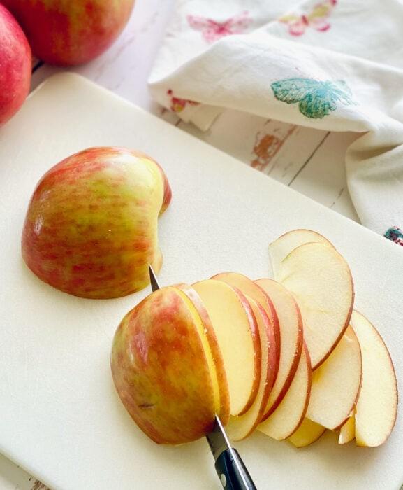 knife slicing through honeycrisp apples.