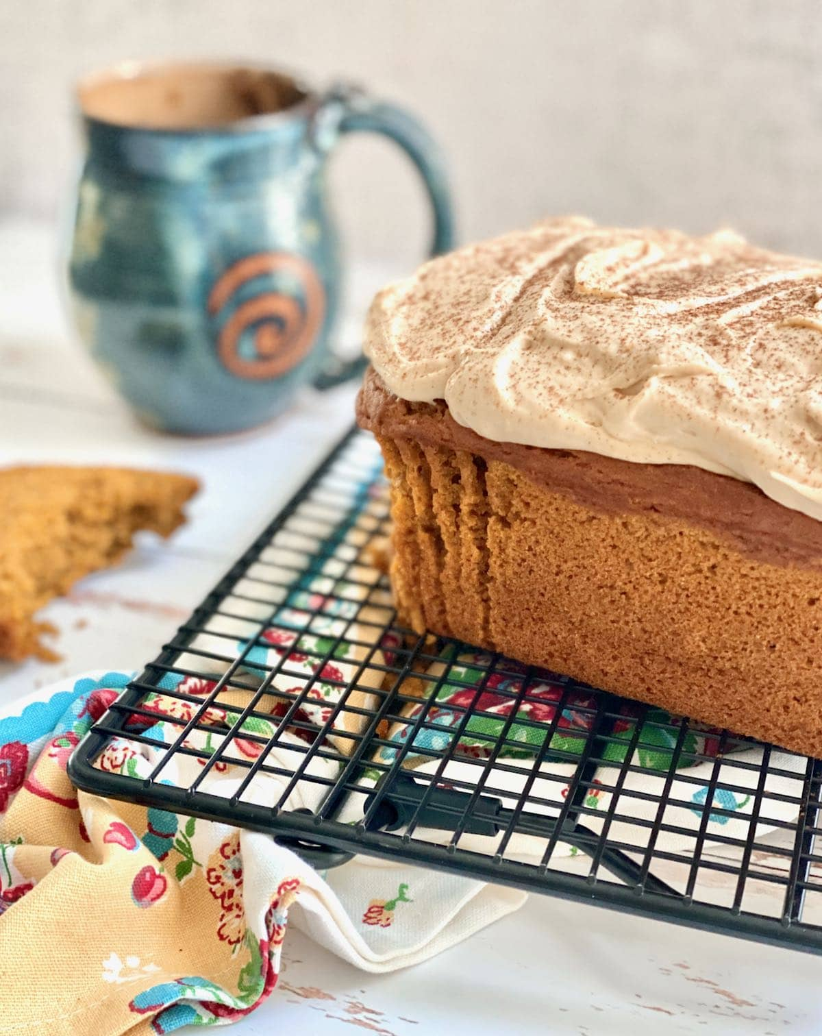loaf of pumpkin bread frosting and cooling on a rack with a coffee cup in background.