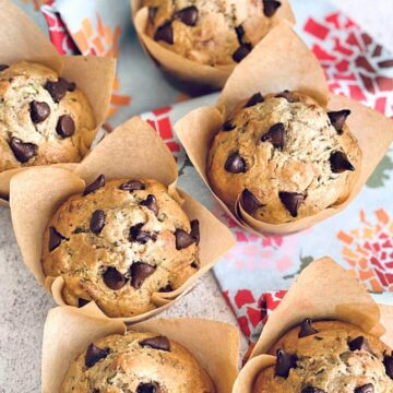 zucchini chocolate chip muffins on a floral towel.