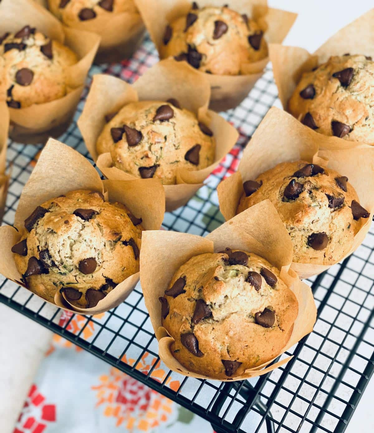muffins on a rack with a floral towel underneath.