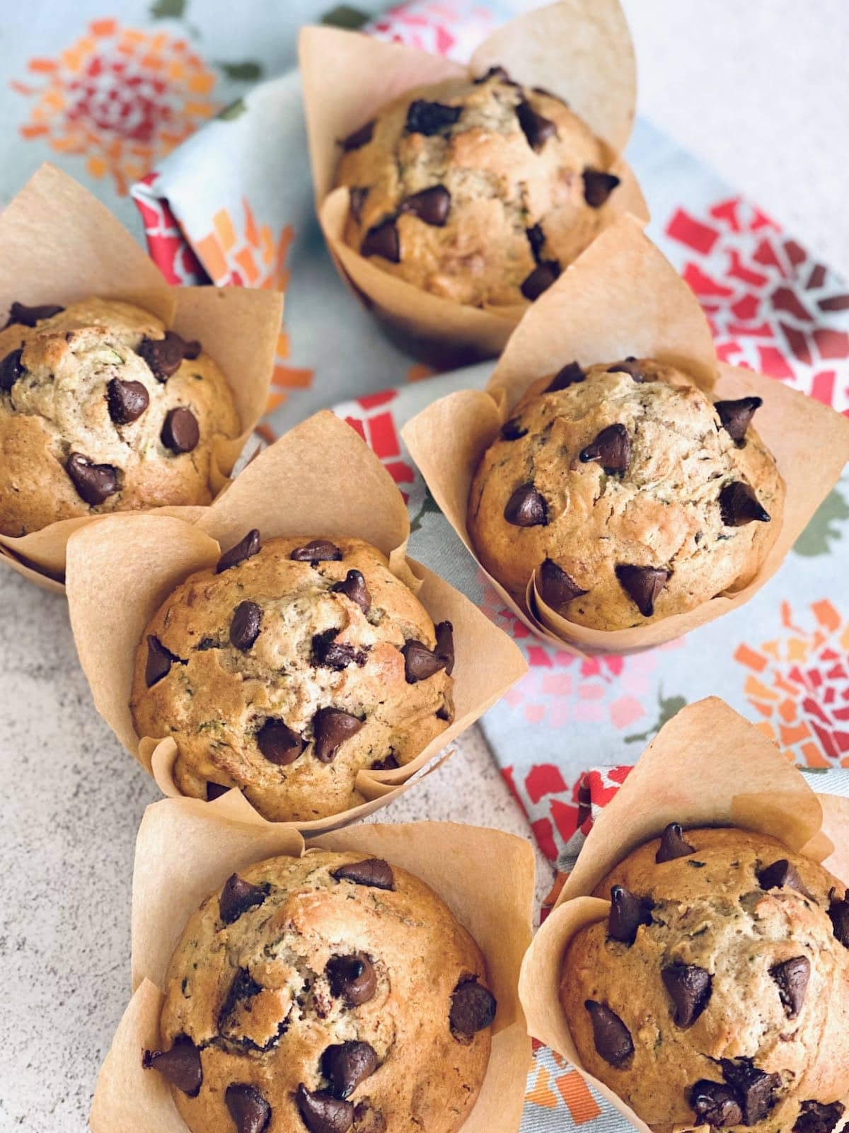 zucchini chocolate chip muffins lined up in a row.