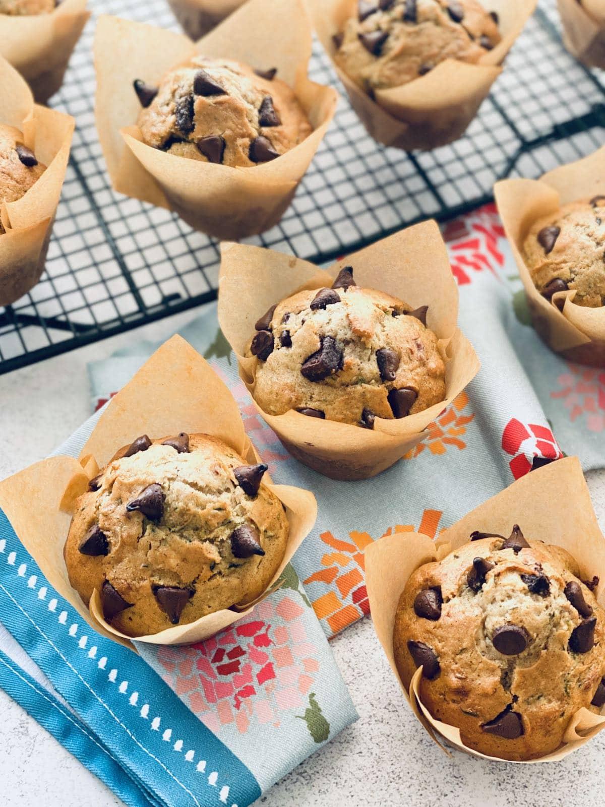 zucchini chocolate chip muffins on a baking rack.