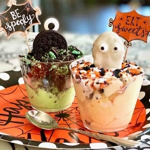 ice cream in cups with halloween monsters and ghosts holding up signs.