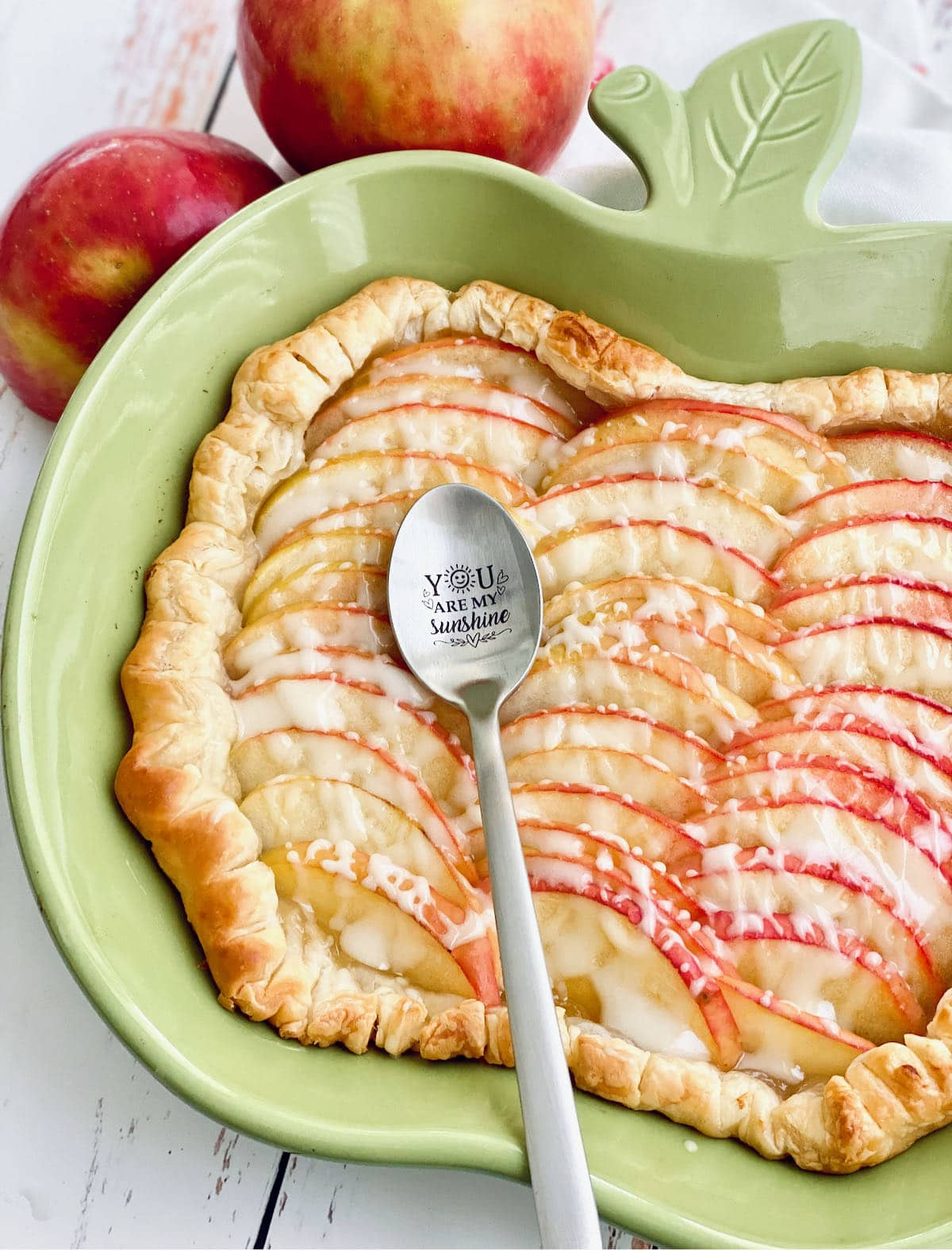 sliced apples arranged on puff pastry in a green apple shaped dish with a spoon on top