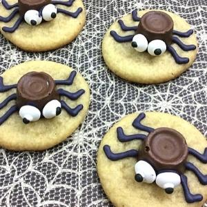 sugar cookies with rolo chocolate spiders on top.