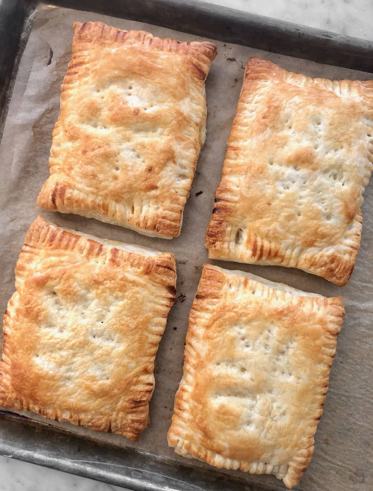 hand pies after being baked on a sheet pan.