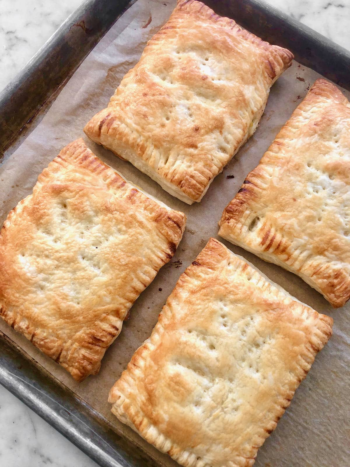 chicken pot hand pies coming out of the oven on a sheet pan.