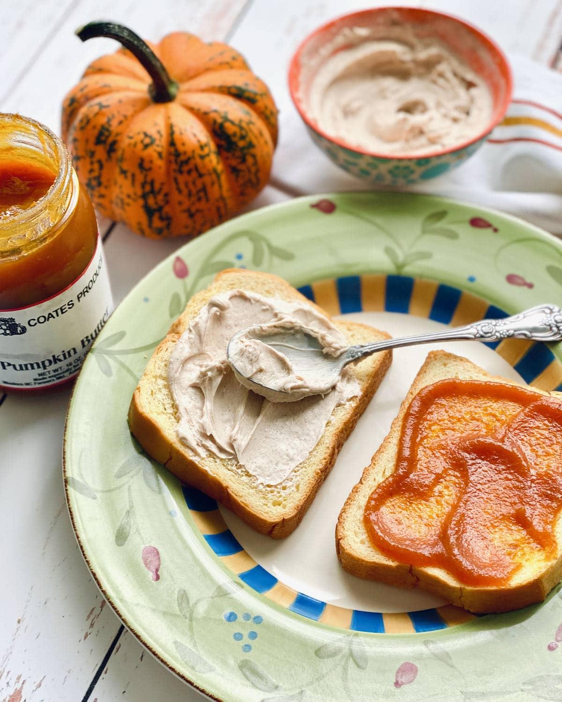 spoon spreading cream cheese and pumpkin butter on brioche bread.