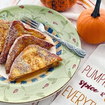 slices of pumpkin spice french toast on a green plate with pumpkins in the background.