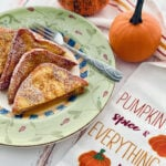 pumpkin spice french toast cut in half on a green plate.