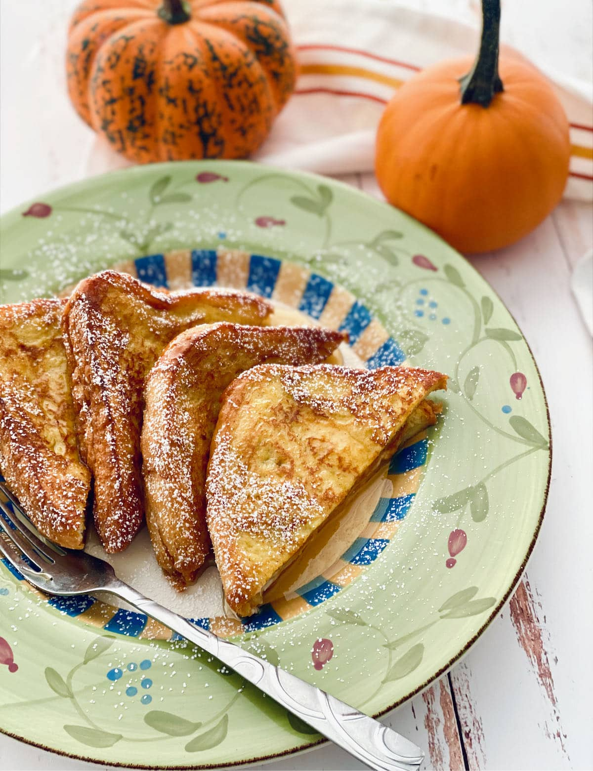 four slices of french toast with pumpkins in the background.