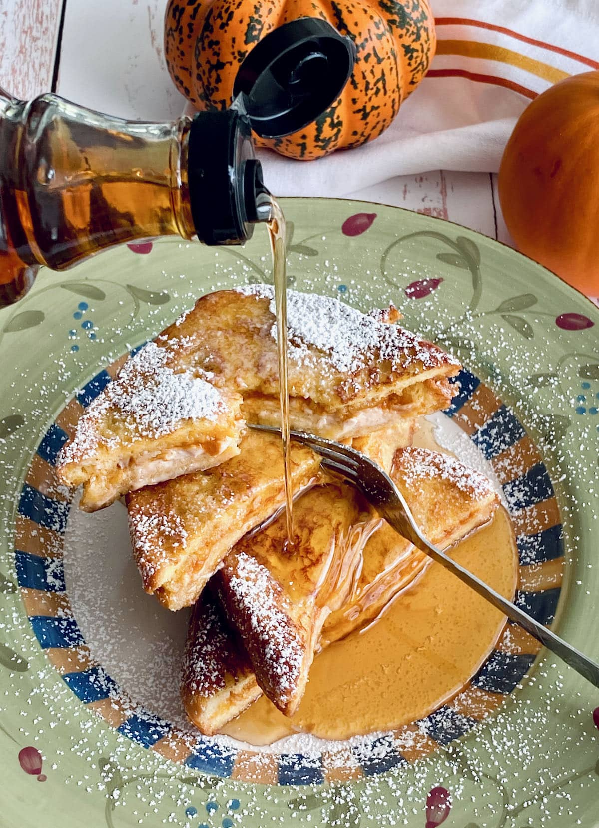 maple syrup being poured over french toast.