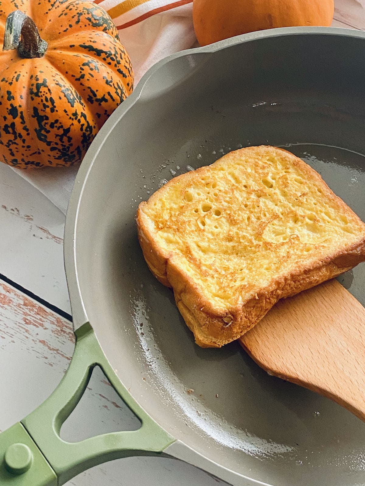 french toast being fried in a skillet.