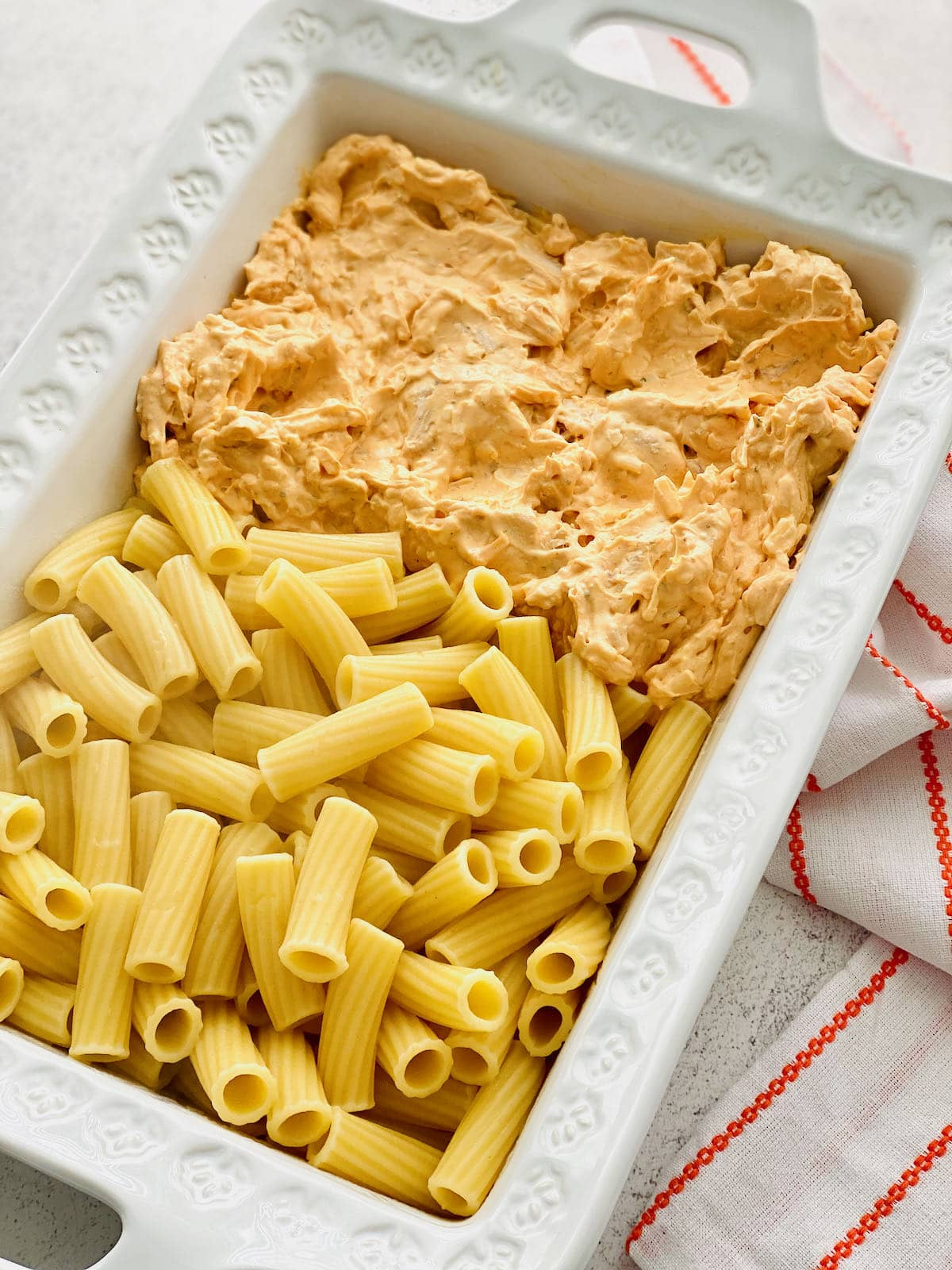 pasta and buffalo chicken dip together side by side in a white dish.